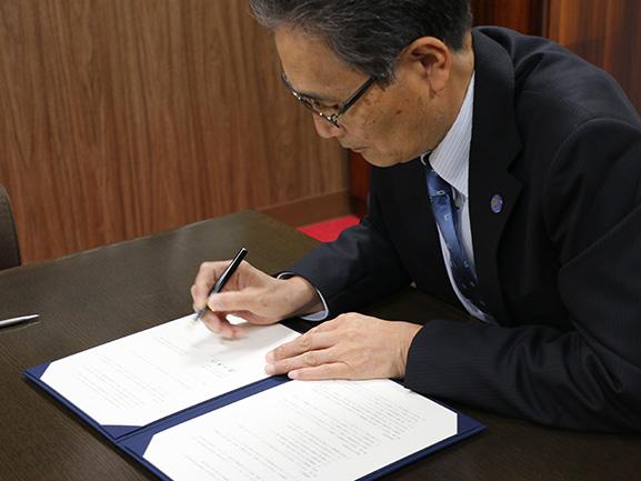協定書に署名する福田学長